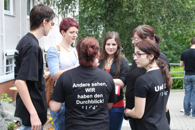 """Eine Gruppe von Schülern unterhält sich, auf einem T-Shirt ist """"Andere sehen, wir haben den Durchblick"""" zu lesen"""
