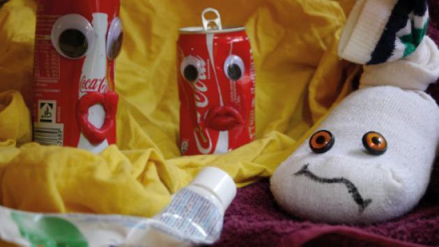 Coladosen und ein Strumpf mit aufgebrachten Gesichtern