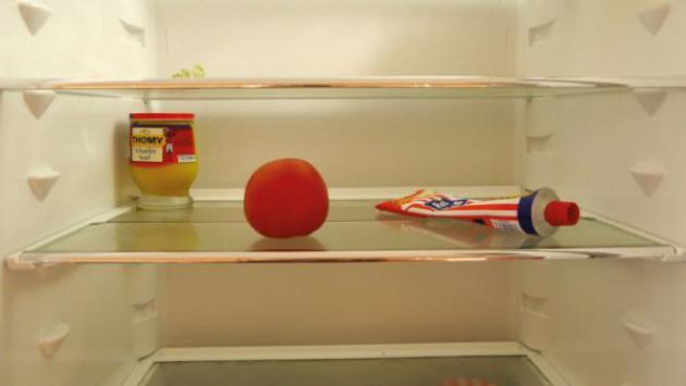Ein Blick in den fast leeren Kühlschrank, man sieht einen Apfel, ein Glas Senf und eine Tube